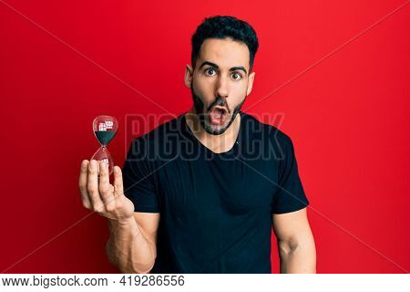 Young hispanic man holding sand clock scared and amazed with open mouth for surprise, disbelief face