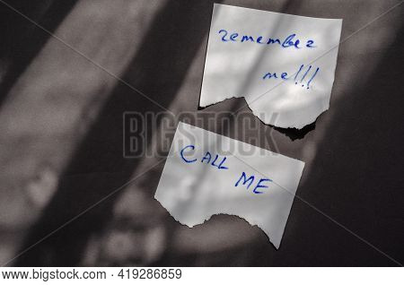 Handwritten Notes Call Me And Remember Me On A White Pieces Of Paper. A Scraps Of Paper With A Jagge