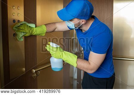 Man Wearing Gloves And A Mask Wipes The Buttons And Handrail Of The Elevator. Cleaning Staff Disinfe