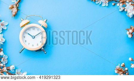 Spring Background May Flowers And April Floral Nature With Alarm Clock On Blue. Branches Of Blossomi