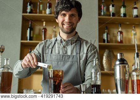 A Professional Bartender Decorates The Cocktail With Lime. The Bartender Prepares A Cocktail With Wh
