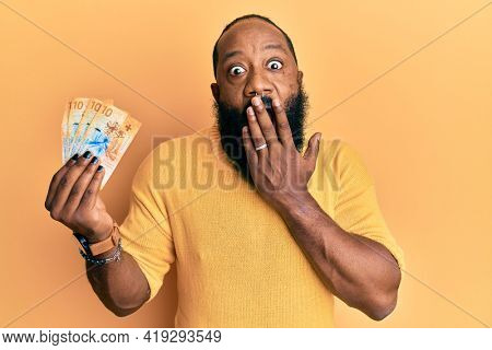 Young african american man holding 10 swiss franc banknotes covering mouth with hand, shocked and afraid for mistake. surprised expression