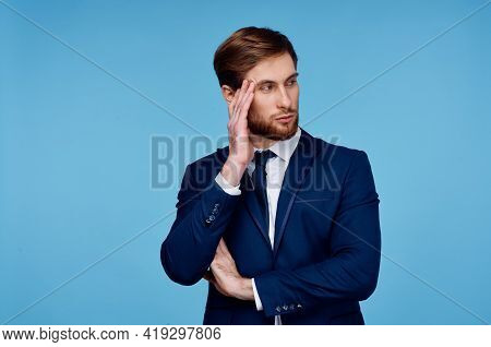 Business Man In A Suit Holds His Hand Near His Head Displeasure Blue Background