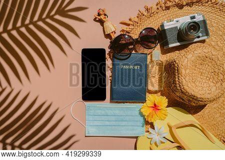Travel essentials to bring on flight during coronavirus pandemic. Flat lay of phone, passport, face mask, hand sanitizer bottle, flip flops, camera, sunglasses, hula doll, sun hat. Caribbean vacation.