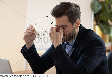Overwhelmed Young Male Manager Taking Off Eyeglasses.