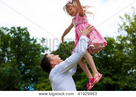 Family affairs - father and daughter playing in summer; he is throwing her into the air