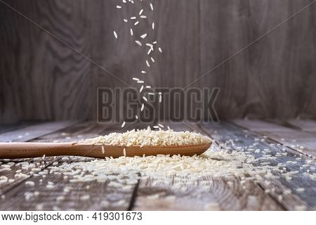 Raw Rice Is Poured From A Wooden Spoon Onto The Table. Rice Groats Are Scattered On The Table. Levit