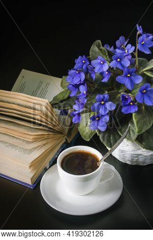 Bouquet Of African Violets With A Cup Of Coffee And An Open Book On A Black Background.