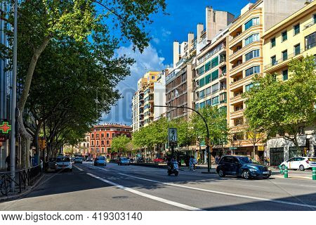 PALMA, SPAIN - APRIL 12, 2019: Urban road, green trees and modern buildings under blue sky in Palma - capital and largest city of Balearic islands, famous resort and tourist destination.