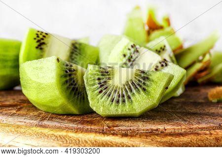 Slices Of Kiwi Fruit On Kiwi Background.fresh Kiwis On Wooden Ground