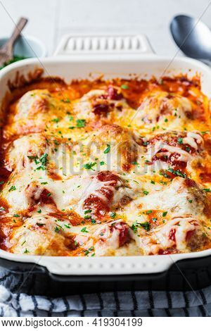 Baked Cheesy Meatballs Casserole With Tomato Sauce In The Oven Dish.