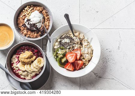 Assorted Oatmeal Bowls With Chocolate, Fruit And Yogurt, Gray Tiles Background. Healthy Breakfast Co