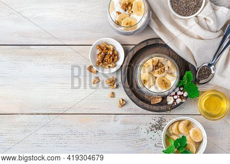 Creamy Banana Pudding With Chia Seeds And Oatmeal Milk, Nuts And Honey On A Light Wooden Background.