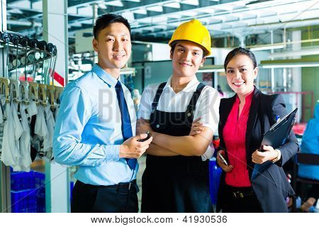 Chinese Shift supervisor or foreman, together with the owner or CEO and the Manager, standing proud in a factory
