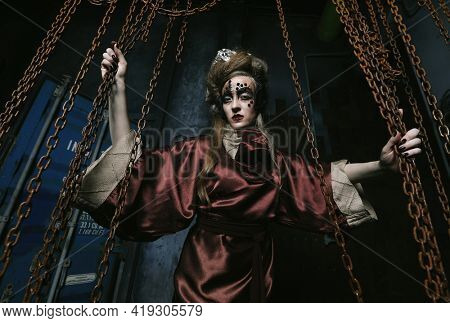 woman with bright makeup in a steampunk scenery holds with her hands for red chains.