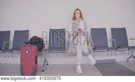 Woman With Phone Is Waiting At Train Station. Action. Beautiful Woman Is Waiting For Flight In Waiti