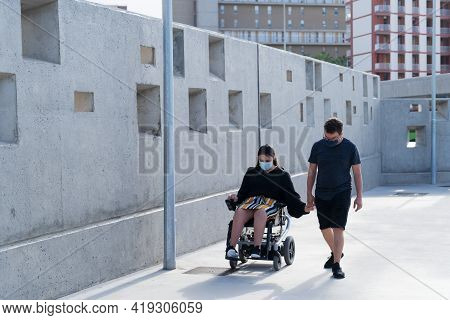 Young Disabled Woman In Wheelchair And Her Loving Boyfriend Or Husband Holding Hands During Covid 19