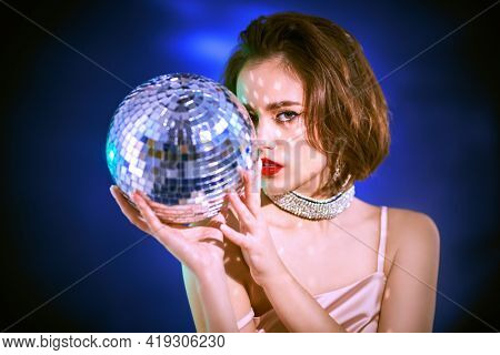 Party and holiday style. Portrait of a glamorous young woman with evening make-up and hairstyle posing in elegant evening dress with disco ball in her hands. Beauty, Fashion and Jewelry.
