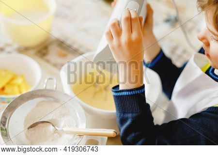 Closeup Of Little Kid Boy Baking Chocolate Cake And Tasting Dough In Domestic Kitchen, Indoors. Clos