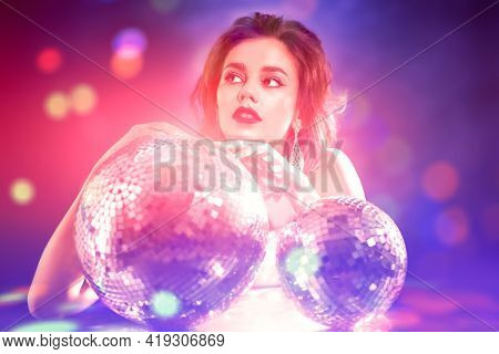 Portrait of a glamorous young woman with evening make-up and hairstyle posing in jewelry with disco balls. Fashion and Jewelry. Beauty. Party and holiday style.