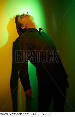 Emotional young man stands, sad and alone, leaning against the wall in dark green and yellow lighting. Feelings and emotions.