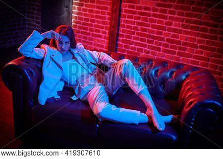 Attractive brunette woman lying on a sofa in a dark room in mixed light. Glamorous lifestyle, luxury.