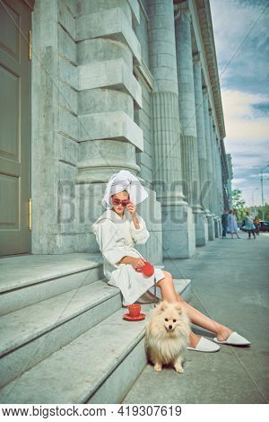 Stunning woman in a white terry dressing gown with a white towel on her head and elegant sunglasses posing  with a cup of tea with spitz on a city street. Glamorous lifestyle. Fashion shot.