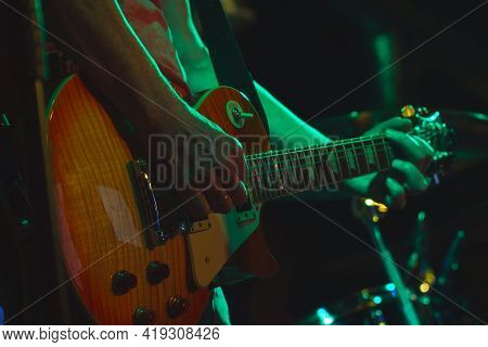 The Guitarist Plays His Guitar In The Spotlight. Hands Of A Guitarist Playing The Guitar. Low Key