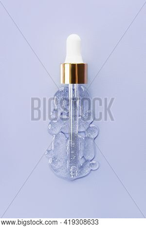 Liquid Serum And Dropper On A Blue Background Top View. Serum Drops In The Form Of A Bottle With A P