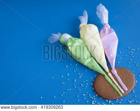 Three Piping Bags With Colored Icing For Cookie Decorating On The Blue Background, Copy Space
