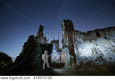 Side View Of Spaceman In Special White Space Suit Walking Near Ancient Ruins And Looking On Stars At