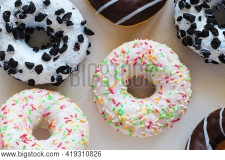 Flat Lay Image Of Donut With White Glaze And Colourful Hundreds And Thousands Amids Other Different