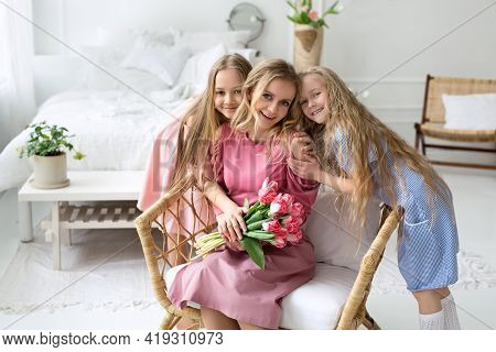 A Mother With Two Daughters Is Sitting In A Chair In The Bedroom With A Bouquet Of Pink Tulips. Moth