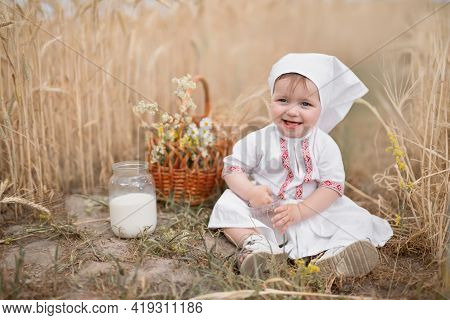A Small Child With A Glass Of Cow's Milk In A Wheat Field. World Milk Day. Fresh, Healthy Milk. Heal