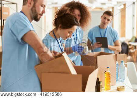 Diverse Volunteers In Protective Gloves Sorting, Packing Canned Food In Cardboard Boxes, Working Tog