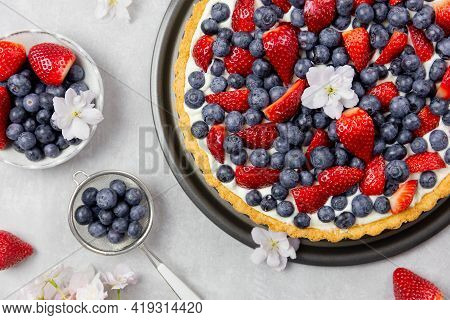 Delicious Blueberry And Strawberry Tart With Whipped Cream And Mascarpone On A Light Gray Concrete B