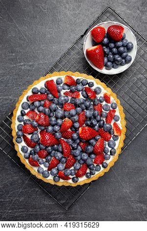 Delicious Blueberry And Strawberry Tart With Whipped Cream And Mascarpone On A Dark Stone Background