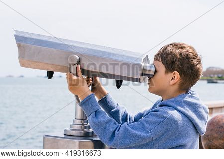 A Blonde Boy Looks Through A City Telescope Against A Background Of Mountains And The Sea