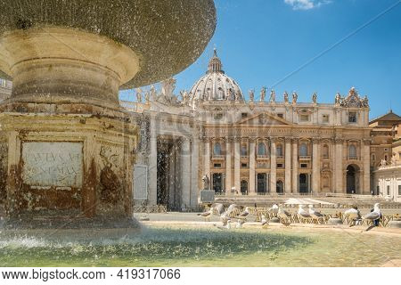 HIstoric fountain of the St. Peter square with St. Peter Cathedral Basilica at background in Vatican city center of Rome, Italy. Famous travel and religious tourist landmark.