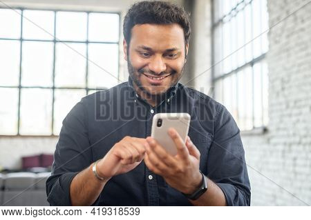 Positive Indian Guy Using Smartphone For Online Communication, Smiling Mixed-race Guy Browsing, Scro