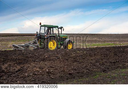 Baykivtsi, Ternopil Region, Ukraine - April 20, 2021: A Tractor 90s John Deere 2850 With A Homemade
