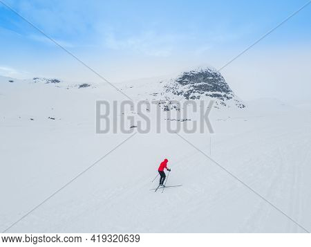 Lonely Frozen Road Winding Through A Snow Covered Mountain Landscape.
