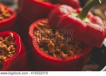 Sweet red peppers stuffed with meat and tomato in a vintage frying tray. Top view