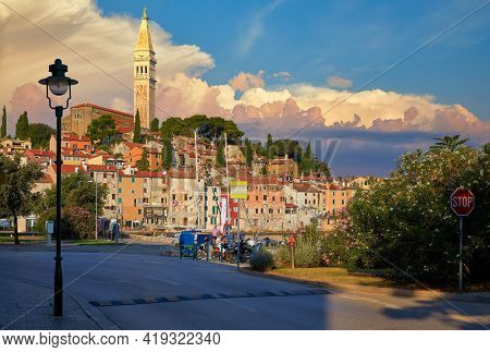 Rovinj, Istria, Croatia. Sunset in medieval old village town of Rovigno, colorful houses and ancient tower during morning sunrise. Picturesque scenic sky with clouds and street lamp by the road.