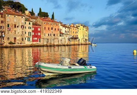 Rovinj, Istria, Croatia. Sunset in medieval old village town of Rovigno, colorful houses and boat in the harbor during morning sunrise. Picturesque scenic sky with clouds and blue water reflections.