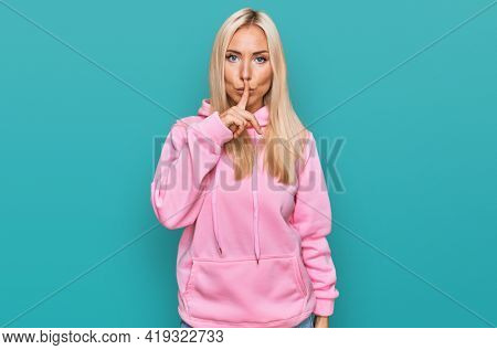 Young blonde woman wearing casual sweatshirt asking to be quiet with finger on lips. silence and secret concept.