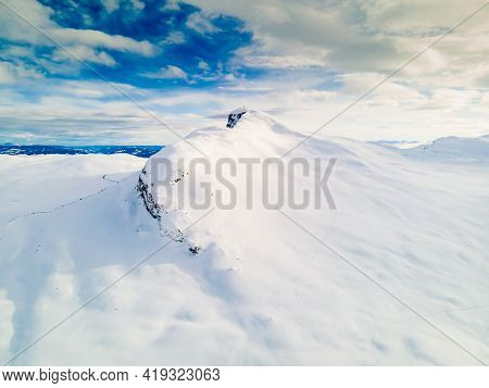 Panoramic View Of A Snow Capped Mountain Peak With Clouds And Blue Skies.