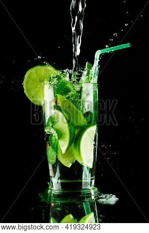 Pouring fresh mojito cocktail in glass notion ice splashing isolated on black background