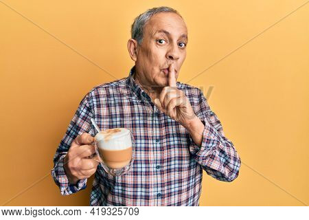 Handsome senior man with grey hair drinking a cup coffee asking to be quiet with finger on lips. silence and secret concept.