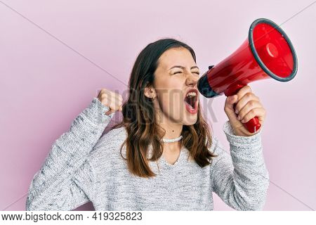 Young brunette woman shouting and screaming through megaphone over pink isolated background